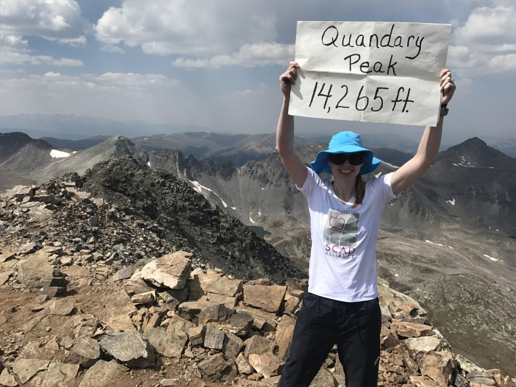 Becky Pomerleau holding a sign saying Quandary Peak 14,265 feet at the top of that peak.