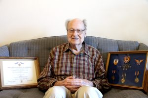 Lt. Veron Bignham sits on the couch with his framed Army Airforce awards and metals.