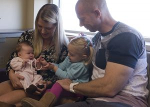 Melissa and Sean Keel look on as Cali, 2, works a high-five with her two-month-old sister Harper. Melissa and Harper were there for the first of six visits she and Harper will make to UCHealth University of Colorado Hospital during Harper's first year, as a part of a major diet study for women with gestational diabetes.