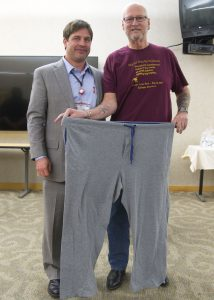 ennis Lawson, right, with the pants he wore the day of his bariatric surgery a year before. Jonathan Schoen, MD, left, performed it.