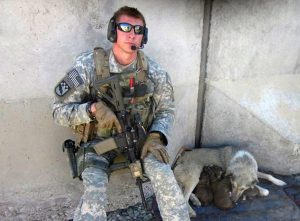 Army Sergeant Spencer Milo in Afghanistan leaning next to a wall with a dog and puppies sleeping beside him.