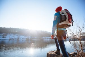 hiker on the edge of a lake in the winter