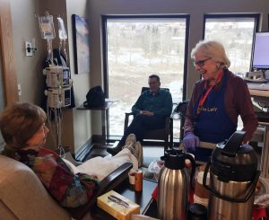 """Joan Gibbs, known as """"The Cookie Lady,"""" is shown distributing cookies to a patient at the UCHealth Jan Bishop Cancer Center in this photo."""