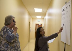 Ruby Vianzon, a professional research assistant with the CU School of Medicine's Emergency Department, is shown leading Gayle Craun through a contrast-sensitivity eye test.