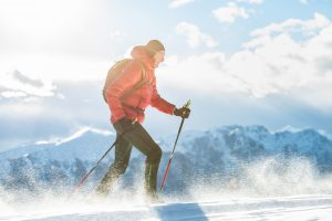 A man is shown skiing in the mountains. Many people in Colorado experience various stages of altitude sickness every day.