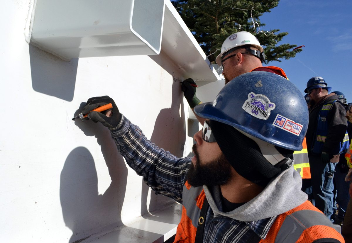 A plumber signs his name on a beam that was placed at one of the highest points of the UCHealth Greeley Hospital building, which is under construction.