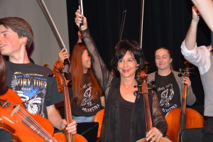 Andrea Meyer raises her cello bow at the completion of an orchestra performance.