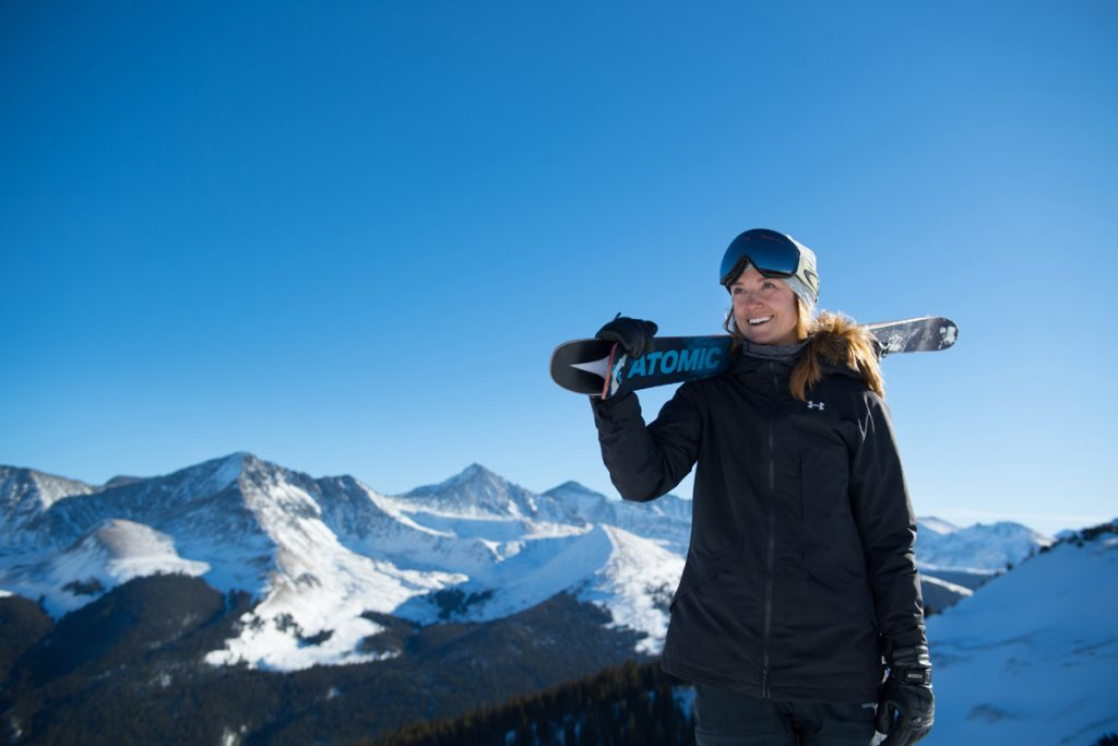 Allie Welsh poses with her skis at the top of Copper Mountain with peaks in the background. She's trying to make it to the Olympics in halfpipe skiing.