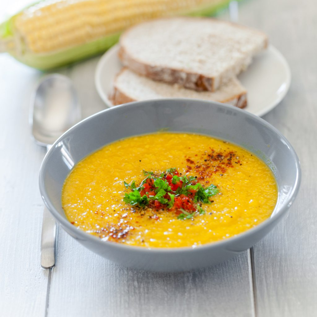 Bowl of vegan corn chowder, garnished with red and green vegetables and dusted with paprika. In the background are slices of bread and an ear of corn.