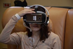 Hannah sits in a chair during a treatment. She wears virtual reality goggles so she can travel virtually while undergoing medical treatments.
