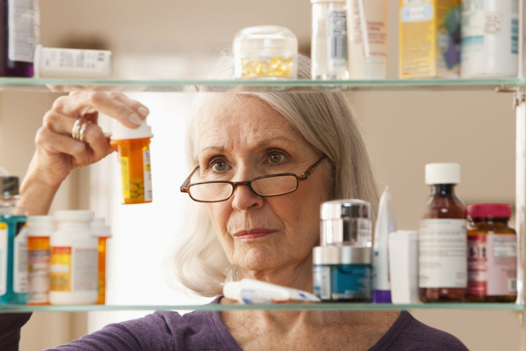 An older woman with glasses reads prescription medication labels.