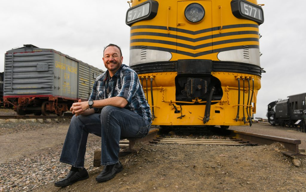 Train engineer Stephen Mullen poses in front of a yellow train. He learned he had a brain tumor that threatened his hearing.