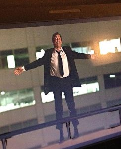 Actor Jordan Leigh looks like he's jumping off a building wearing a business suit as he films a stunt shot for a soon-to-be-released film, Stadium Anthems.