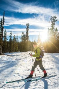 A cross-country skier glides across a snowy meadow.
