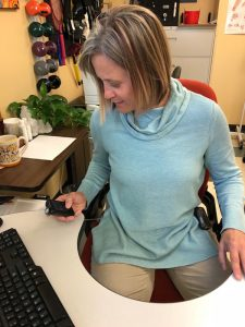 Diabetes patient Tia Mollander sits at her desk and looks down at an insulin pump.