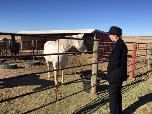 Marcy Brossman visits with one of the family's horses on their property in Cheyenne Wells, Colorado.