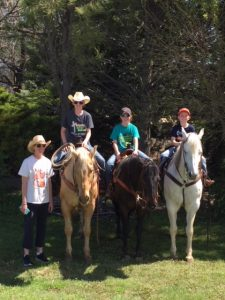 Marcy Brossman and her children on an outing with their horses.