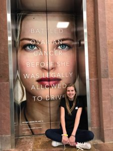 Peyton sits in front of an elevator tht shows her in her UCHealth ad.