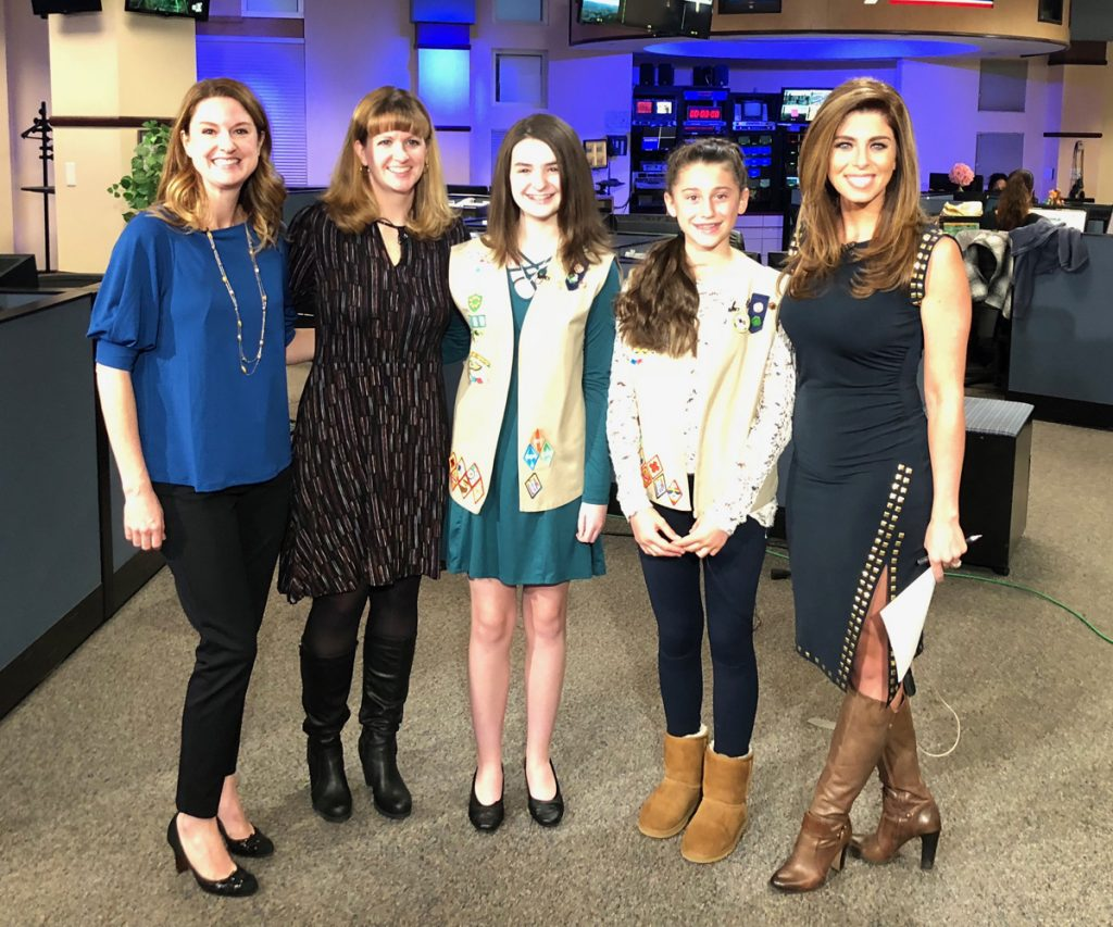 Kathleen Moreira of UCHealth tobacco treatment specialist poses with Girl Scouts and 9 News anchor, Corey Rose, after the girls persuaded the Aurora City Council to pass a smoking ban.