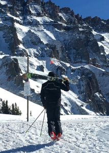 Jonathan Greenspan carries his skis, headed higher than a lift will take him.