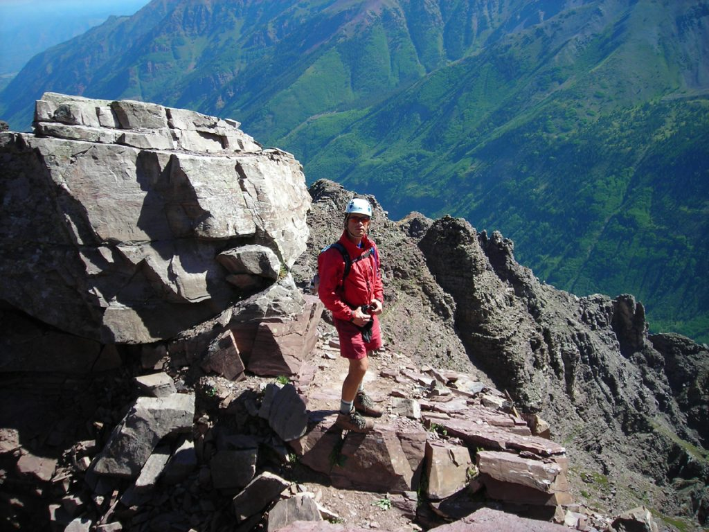 Patrick Gaines poses on a rocky outcropping on a Colorado peak. He has used alternatives to opioids and exercise in dealing with chronic pain.