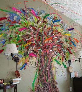 A giant tree made of art sprouts on a wall at Patrick Gaines' house. He uses art along with other alternatives to opioids to deal with chronic pain.