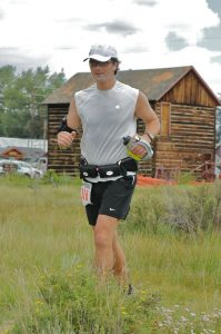 Patrick runs and uses alternatives to opioids to cope with chronic pain. Here, he is running in the mountains with a barn behind him.