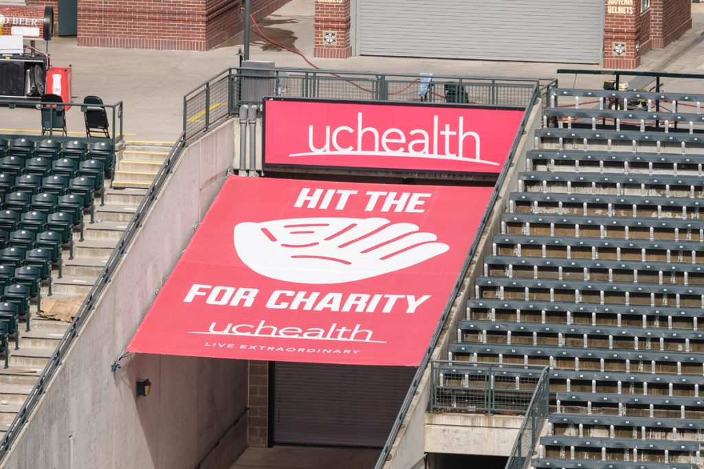 """A red """"Hit the Mitt"""" sign at Coors Field in Denver. The sign shows a big mitt with Hit the Mitt spelled out around it and UCHealth at the top. Each time a Rockies player hits a homer that strikes the sign this year, $5,000 will be donated to help with food insecurity in Colorado.."""
