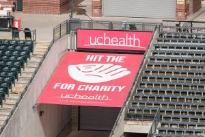 "A new red ""Hit the Mitt"" sign at Coors Field in Denver. The sign shows a big mitt with Hit the Mitt spelled out around it and UCHealth at the top. Each time a Rockies player hits a homer that strikes the sign this year, the Gold Crown Foundation will get $5,000."