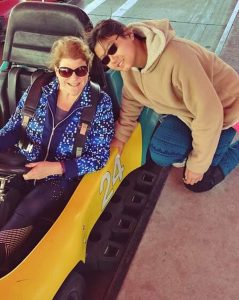 Cella and Lilly Roberts enjoy having fun together. Here they ride in a race car at an amusement park.