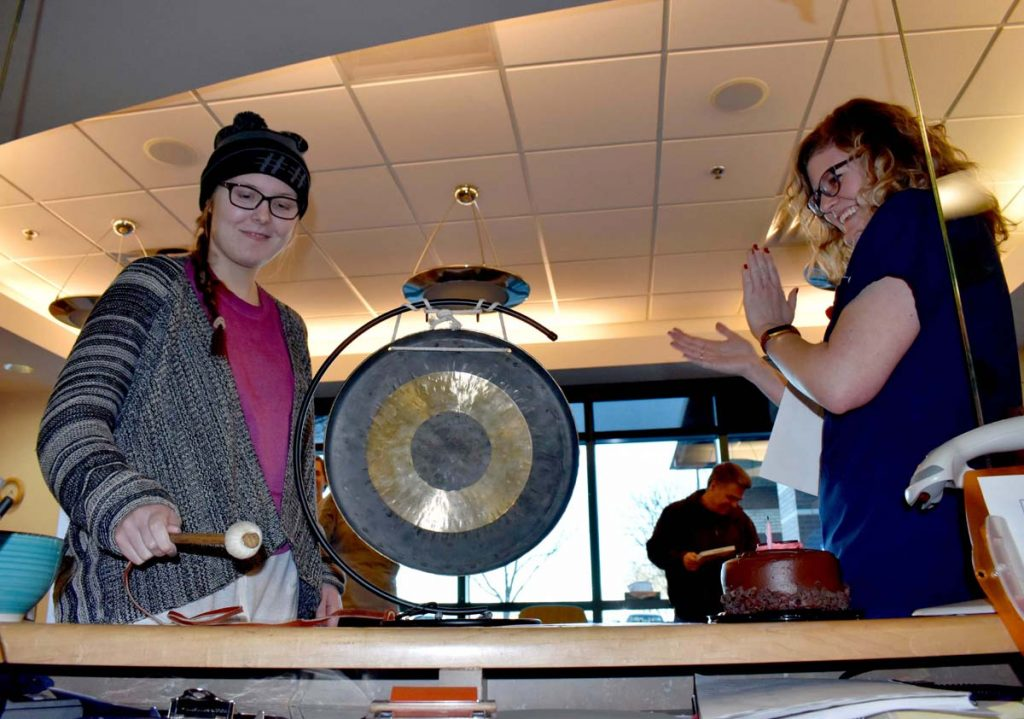 A photo of Kate Prewett banging a gong after radiation treatment.