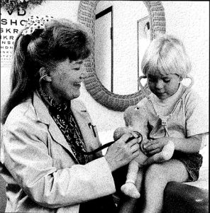 Dr. Jeanne Lewis in a 1994 photo from the Boulder Daily Camera. She's wearing a white coat and using her stethoscope to check on a young patient.