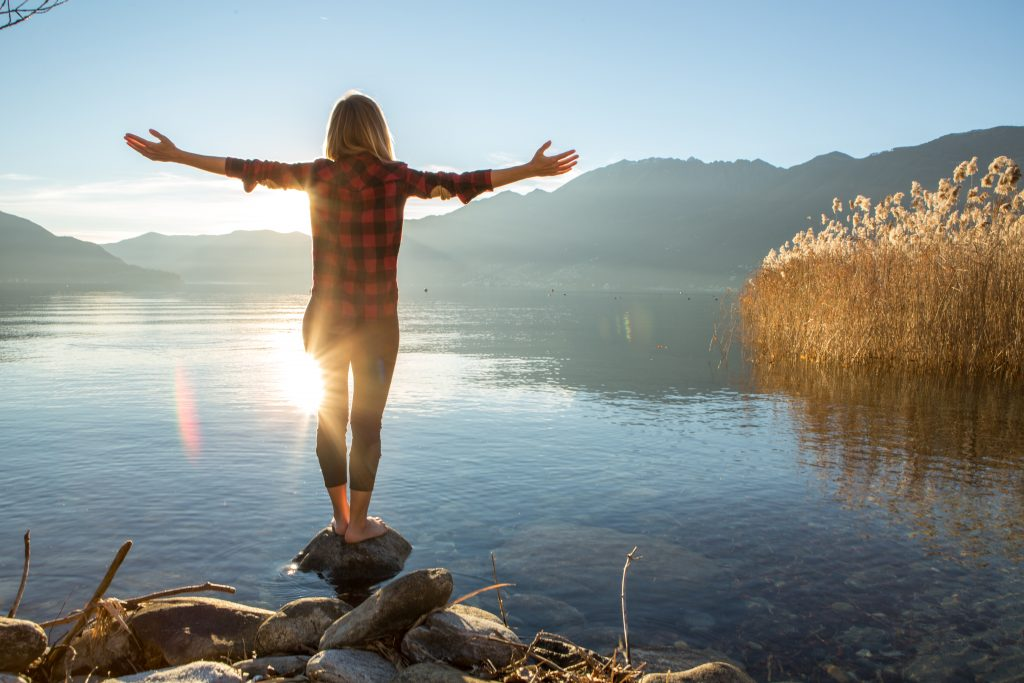 A woman balances on a rock while overlooking a lake.