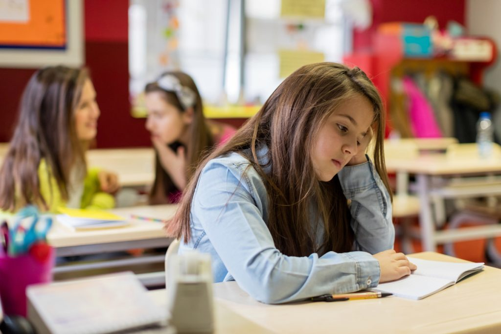A teen girl at a student's desk. She looks depressed.