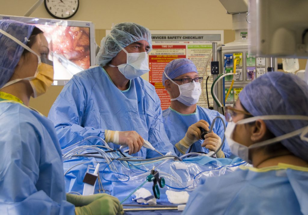 A team of surgeons performs surgery in an operating room at UCHealth University of Colorado Hospital.