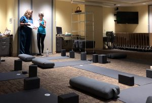 two women talk, while yoga mats lay on the floor