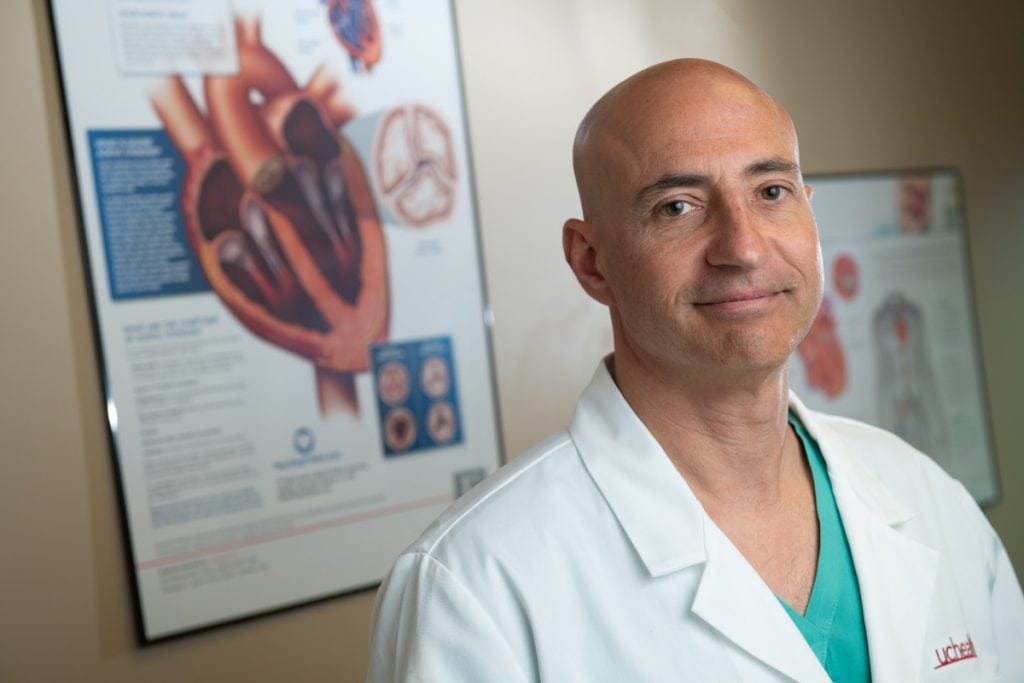 Dr. Peter Walinsky stands in front of a poster that shows the anatomy of the heart.