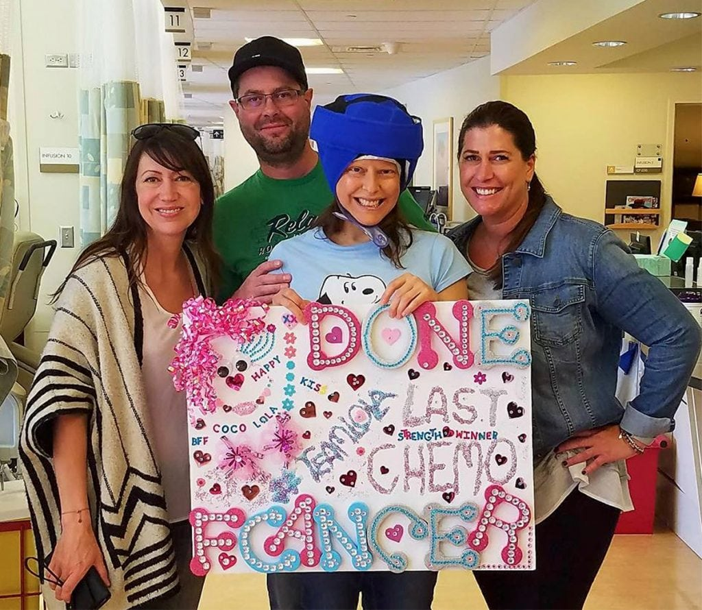 "Louisa Drouet poses with supporters on the last day of chemo. She is wearing a big blue cap. It's called a cold cap and it helps women keep their hair. She's holding a sign that says ""Last chemo"""