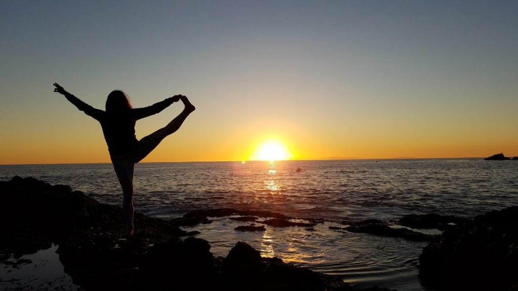 Louisa Drouet holds her leg out to her left as she does a yoga pose on a California beach at sunset.