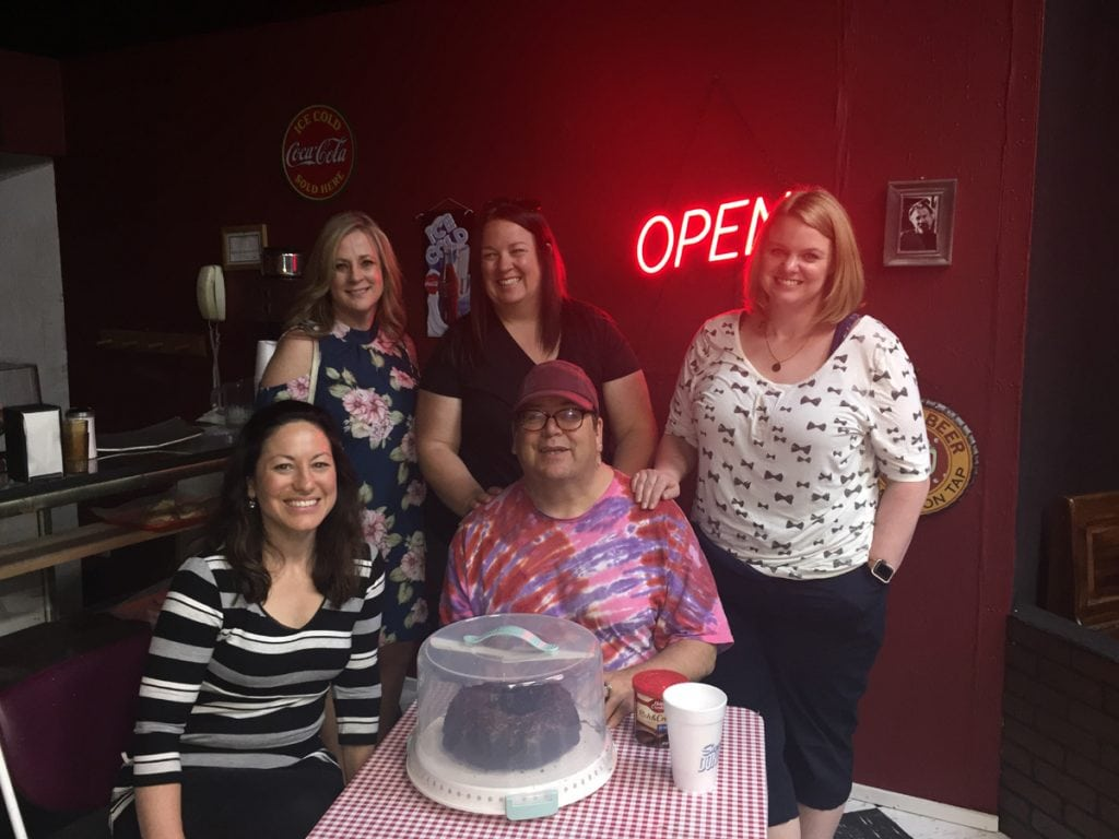 "Greg West and his health care team pose on the set for the play, Superior Donuts. West is thrilled to be back on stage afte rnearly dying from heart failure. They sit around a table with a sign that says ""Open"" behind them."