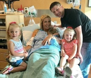 mom in the hospital holding new baby, with dad and two daughters at her side, right before mom experienced placenta accreta.
