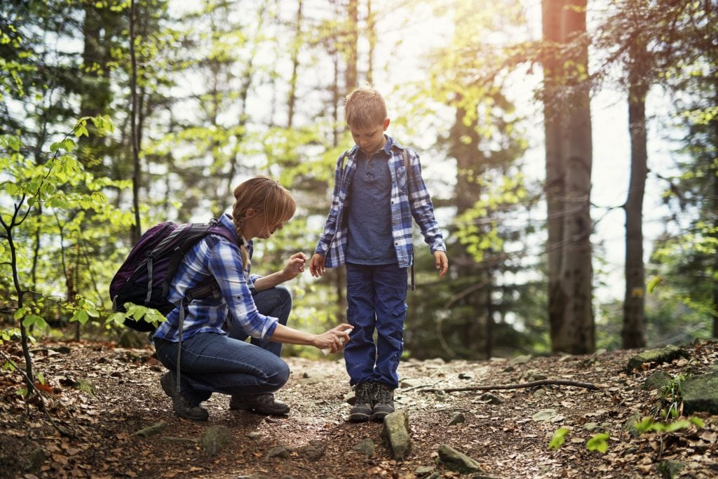 A mother sprays tick repellent on her son's legs while hiking in a forest.