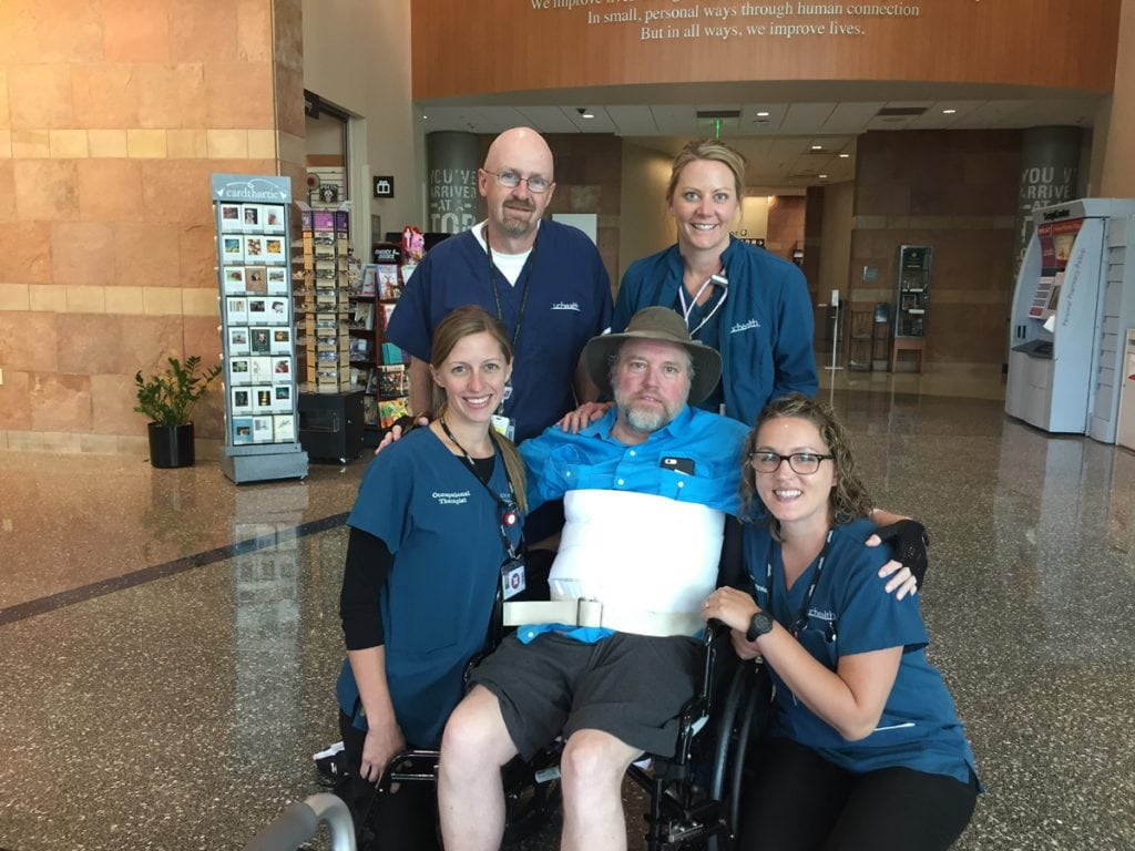 Doug Zirkle, center and sitting in his wheel chair, with members of his care team as he prepares to walk out of the hospital last September.