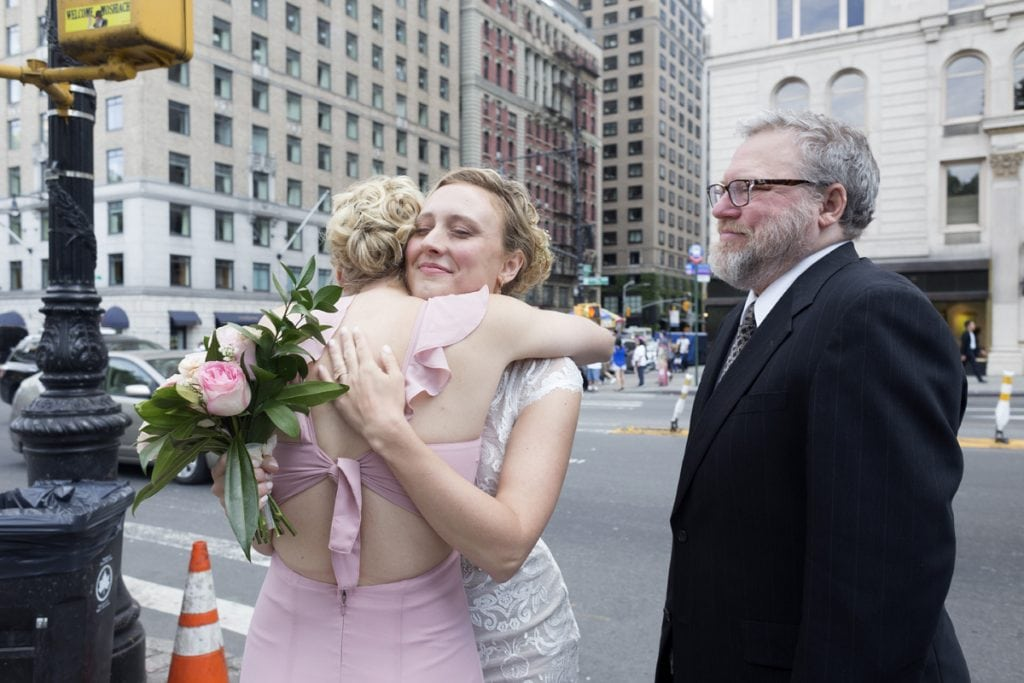 Sisters Laura Zirkle, left, and bride-to-be, Rachel Zirkle, embrace in one last hug before walking down the aisle. Their father, Doug Zirkle, smiles watching the two. Photo by Elaine Cromie for UCHealth.