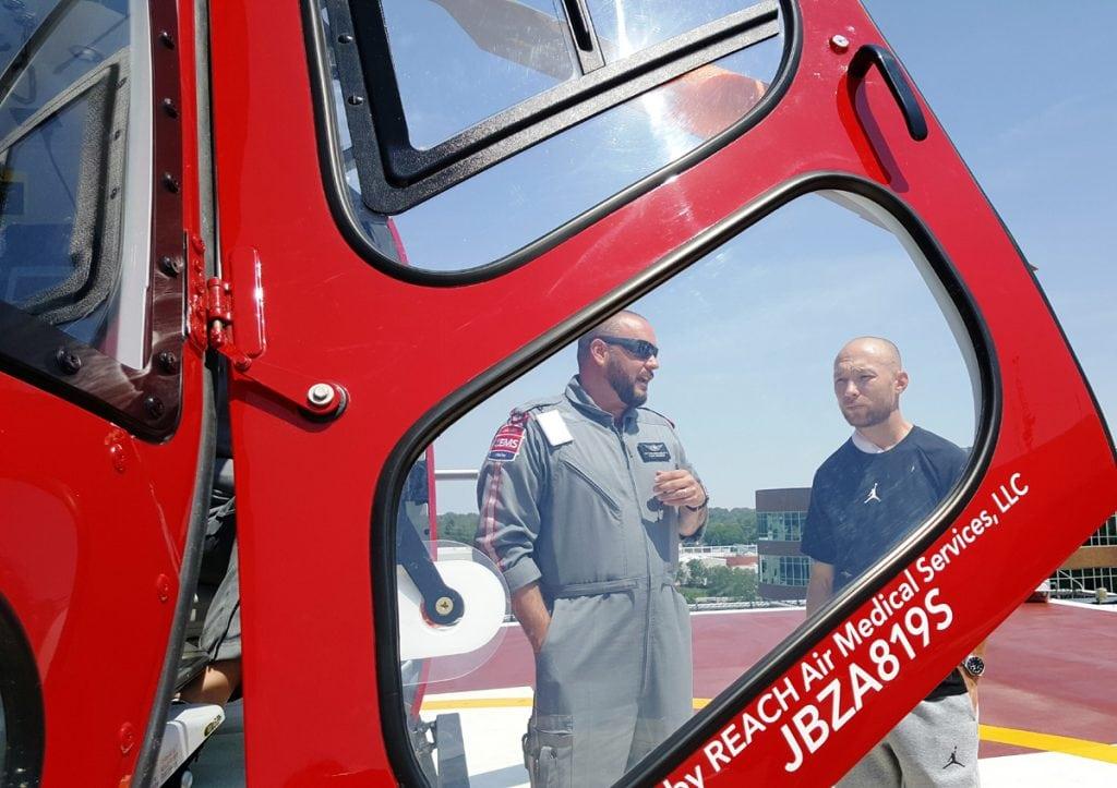 UCHealth Flight Paramedic Matthew Bergland talks to Eddie Kerr near the UCHealth Lifeline helicopter.