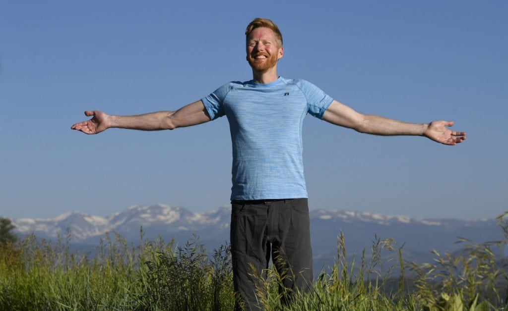 Jonathan Proctor celebrates feeling much better after getting surgery for a condition called pectus excavatum. Here, Jonathan holds his arms out to show how easily he can breathe. Behind him, you see the snow-capped Rockies.