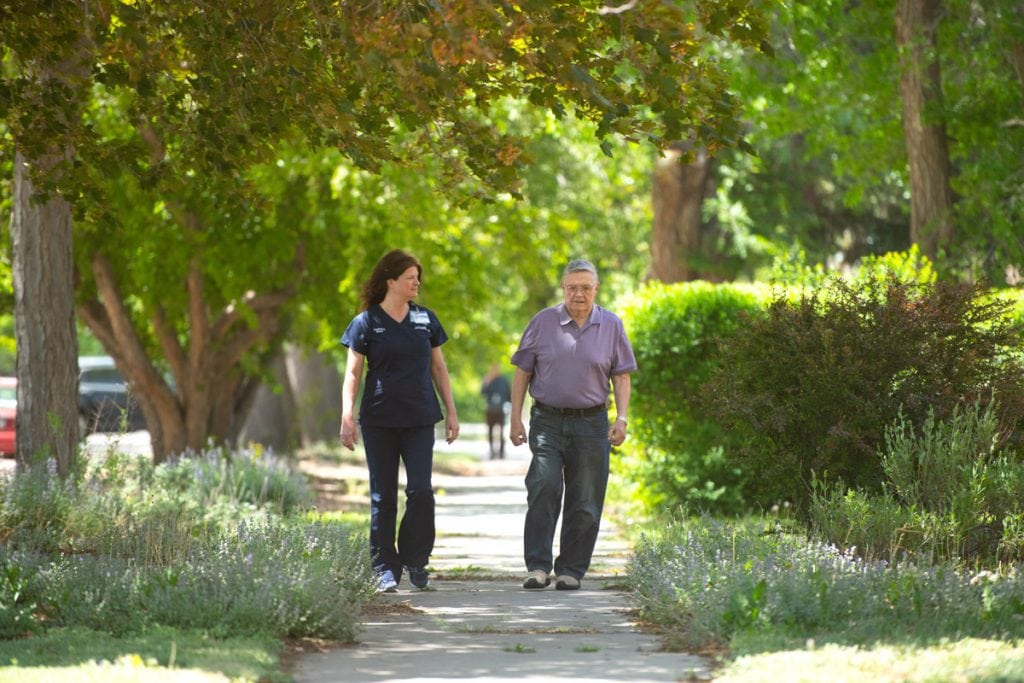 A nurse walking with her patient in a park.