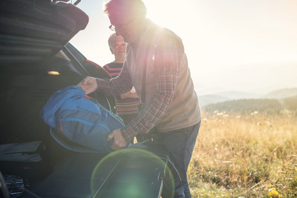 Happy senior couple packing a car trunk and enjoy in the end of great day in nature