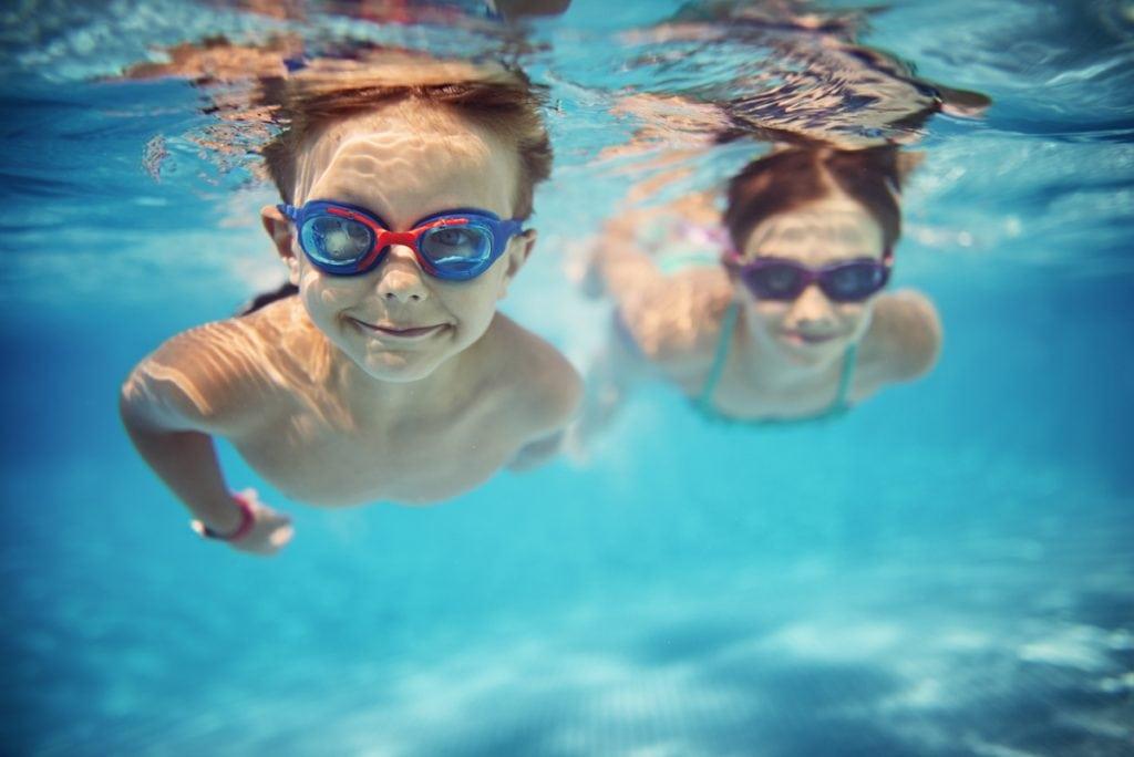 Smiling kids enjoying an underwater swim