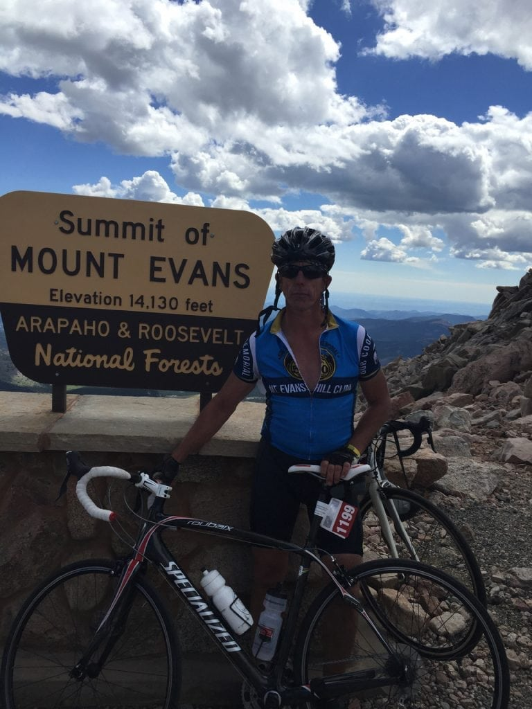 Avid cyclist Rich Trostel is back on his bike thanks to a partial knee replacement. In this photo, he poses at the top of Mt. Evans. Behind him is a sign showing the altitude of the Colorado 14er.